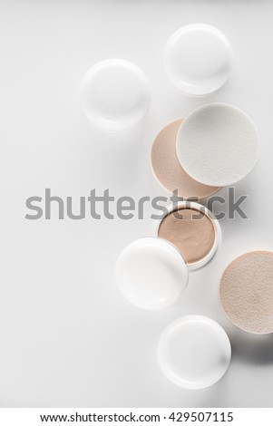 White beige opened and closed jars with concealers for hiding defects of the skin. Perfect cosmetic for applying the foundation. Sponges as tools for putting on the make-up. - stock photo