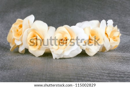 white beige rose in the wedding crown with gold the centers fresh from a cold porcelain on the grey fabrics pearl tint - stock photo