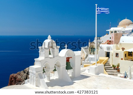 White bell tower and Greek flag in Oia.