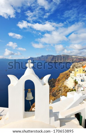 White bell tower overlooking the sea in Oia, Santorini, Cyclades, Greece