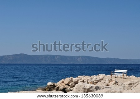 White bench in port with stones and blue sky, island Hvar in background. Podgora, Croatia - stock photo