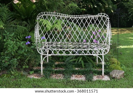 White bench in the green garden