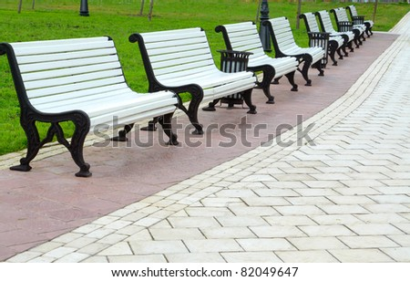 White benches in a park - stock photo