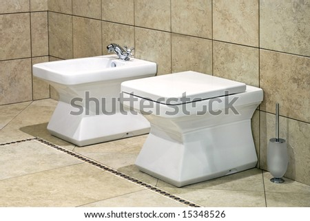 White bidet and toilet in beige lavatory