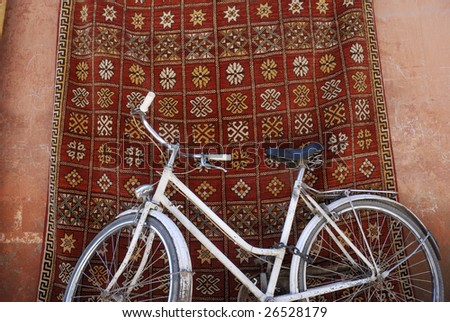 White bike in front of a shop that sells traditional carpets in Marrakesh,Morocco - stock photo
