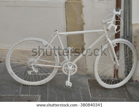 White bike on wall in the streets of Coimbra, Portugal
