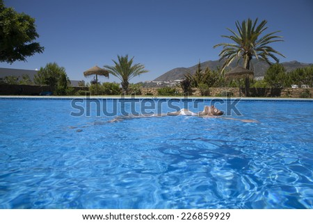 white bikini woman lying on the water in a big blue pool