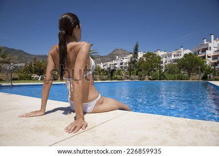 white bikini woman sitting on the curb in a big blue pool - stock photo