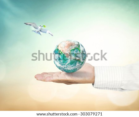 White bird with green leaves to planet in human hand on blurred city sunset background. Holy Bible Whit Monday CSR Earth Hour World Press Freedom Day concept. Elements of this image furnished by NASA. - stock photo