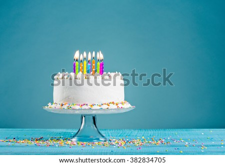 White birthday cake over blue background - stock photo