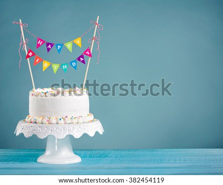 White Birthday cake with colorful bunting and blue background - stock photo