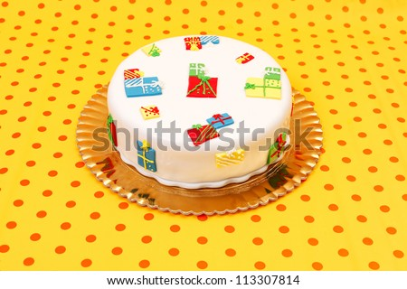 White birthday cake with marzipan ornaments on dotted orange background