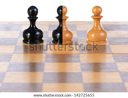 White, black and black-and-white pawns on a chessboard. - stock photo