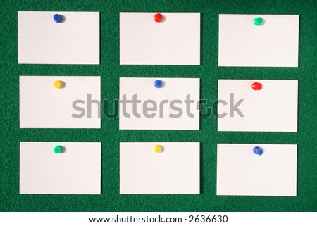 White blank business/advertisement cards pinned to a green felt notice board. - stock photo