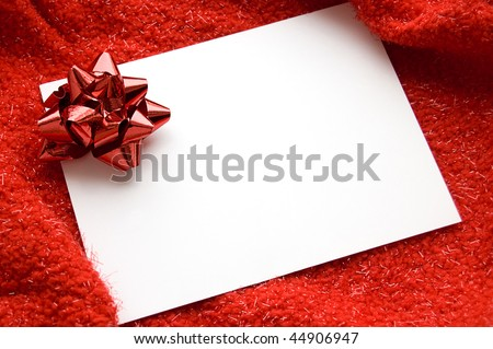 White blank note with red ribbon bow on red background