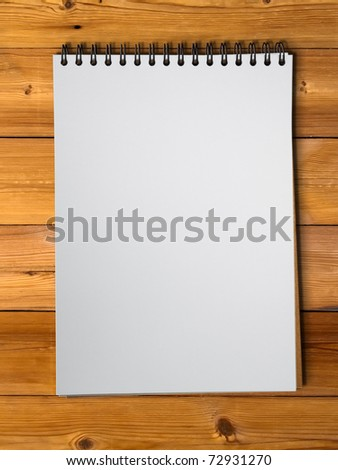 White blank page sketch book on wood table vertical