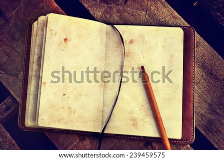 White blank papers in a copybook with a pen on the wooden desk - stock photo