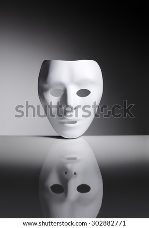 White blank plastic mask on reflective surface. - stock photo