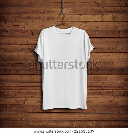 White blank t-shirt on dark wood wall - stock photo