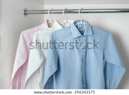 white, blue and pink clean ironed men's shirts hanging on hangers in the white wardrobe