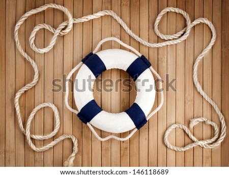 White & blue lifebuoy and marine rope on a wooden background. - stock photo