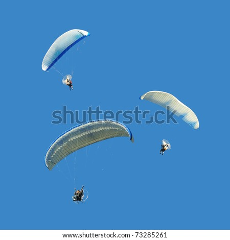 White blue paramotor on blue sky - stock photo