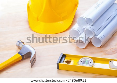 white blueprints construction level yellow helmet claw hammer on wooden board horizontal version  - stock photo