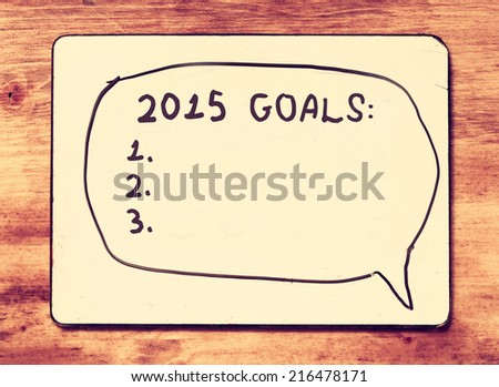 white board with the phrase 2015 goals over wooden table. retro vintage filter - stock photo