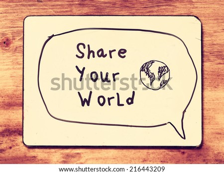 white board with the phrase share your world, over wooden textured background. retro filtered image. concept for social media use or sharing, - stock photo