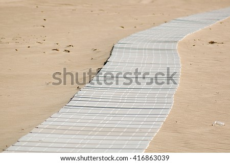 White boardwalk on sandy beach - stock photo