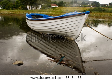 White boat during rainy day with reflections - stock photo