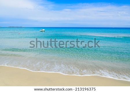 White boat in distance on beautiful turquoise sea water of Porto Giunco beach, Sardinia island, Italy  - stock photo