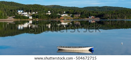 White boat reflected in a calm bay in central Newfoundland