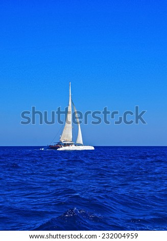 White boat with sails in the Mediterranean - stock photo