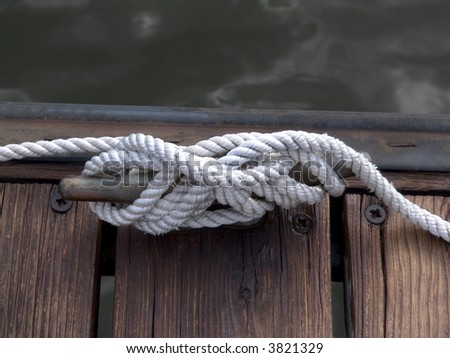 white boater's rope artistically coiled and attached to cleat on dock