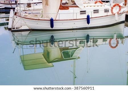 White boats and yachts with their reflections on a water  in the quay