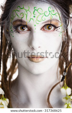 White bodypainted model with dreadlocks looking straight in the lens.