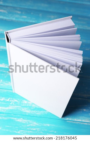 White book on wooden table, close-up - stock photo