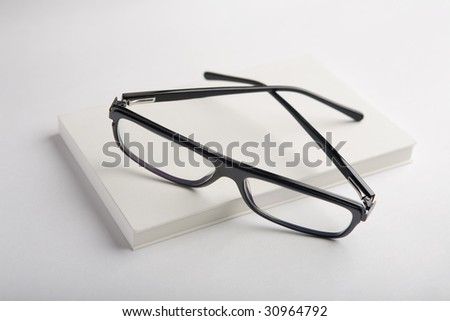white book with black glasses