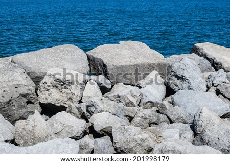 White boulders and rocks against rippled blue water. - stock photo