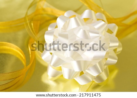 White bow and gold ribbon on reflective surface for Christmas, New Years, birthdays or an anniversary.  - stock photo