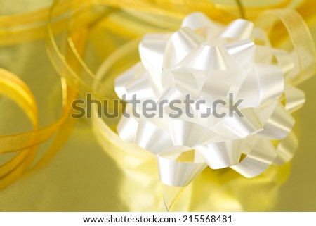 White bow and golden ribbon on reflective surface. Shallow depth of field.  - stock photo