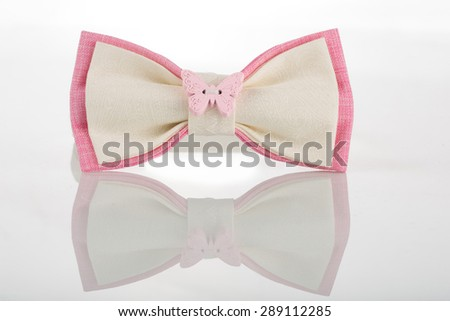 white bow tie with pink accents and a butterfly - stock photo