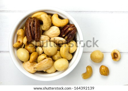 white bowl filled with nuts and a few nuts next to it on a white background - stock photo
