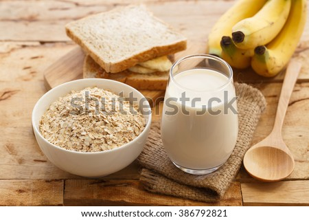 White bowl full of healthy oatmeal, with banana, milk, and dry bread for breakfast. - stock photo