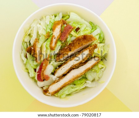 white bowl of caesar salad on color wax paper table top - stock photo