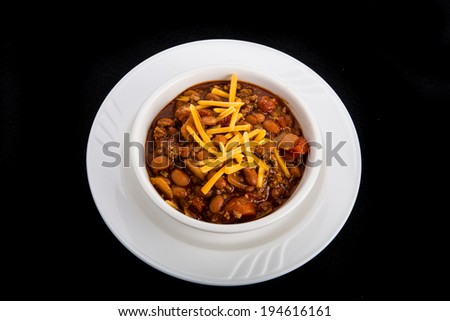 White bowl of chili con carne with beans and grated cheddar cheese on a black background - stock photo