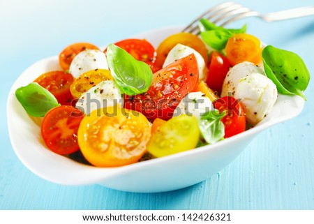 White bowl of fresh and healthy Mediterranean salad with mozzarella cheese, tomatoes and basil leaves and a fork over a blue table - stock photo