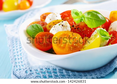White bowl of fresh and healthy Mediterranean salad with mozzarella cheese, tomatoes and basil leaves over a white doily blue table