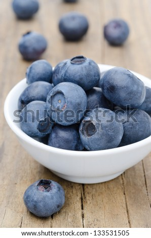 white bowl of fresh blueberries on a wooden background - stock photo